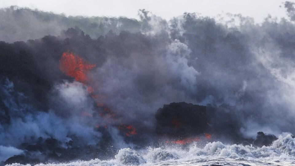 Entourée de fumée, une coulée de lave tombe dans une vague.