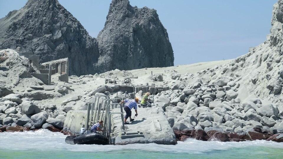 Deux personnes s'affairent près d'un zodiac accosté à un quai sur une rive rocailleuse.