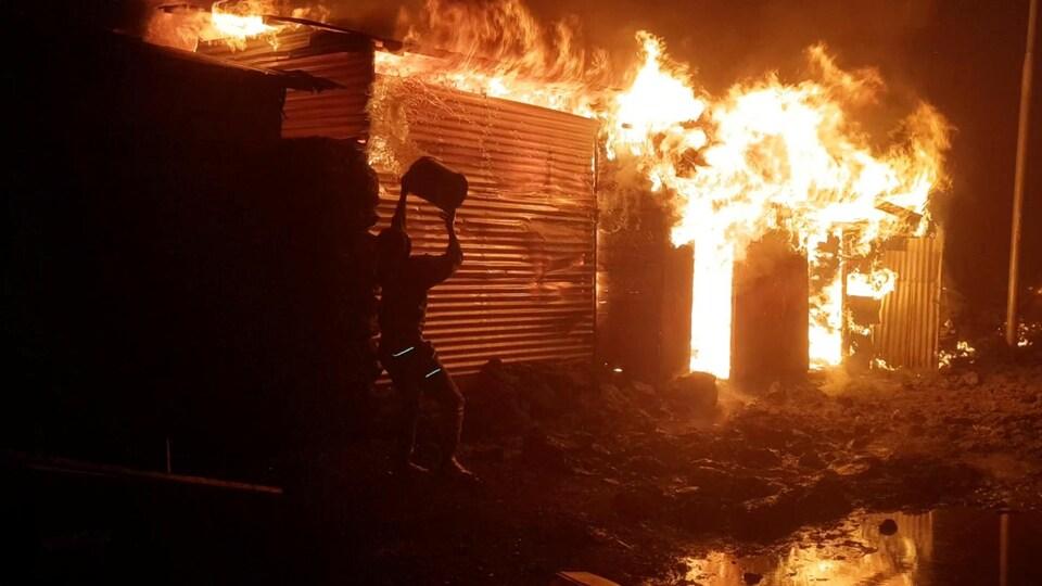Un homme tente en vain d'éteindre un petit bâtiment en tôle envahi par les flammes.