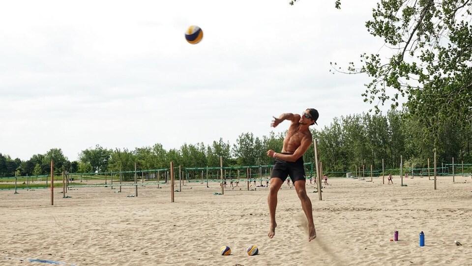 Un joueur de volleyball de plage tape dans le ballon sur une plage.