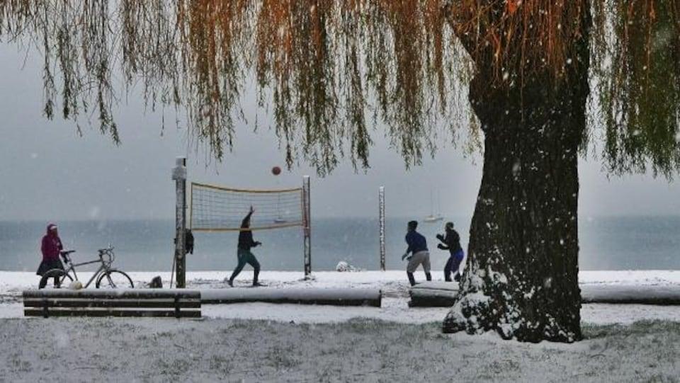 Des passionnés de volley-ball jouent sur une plage enneigée de Vancouver.