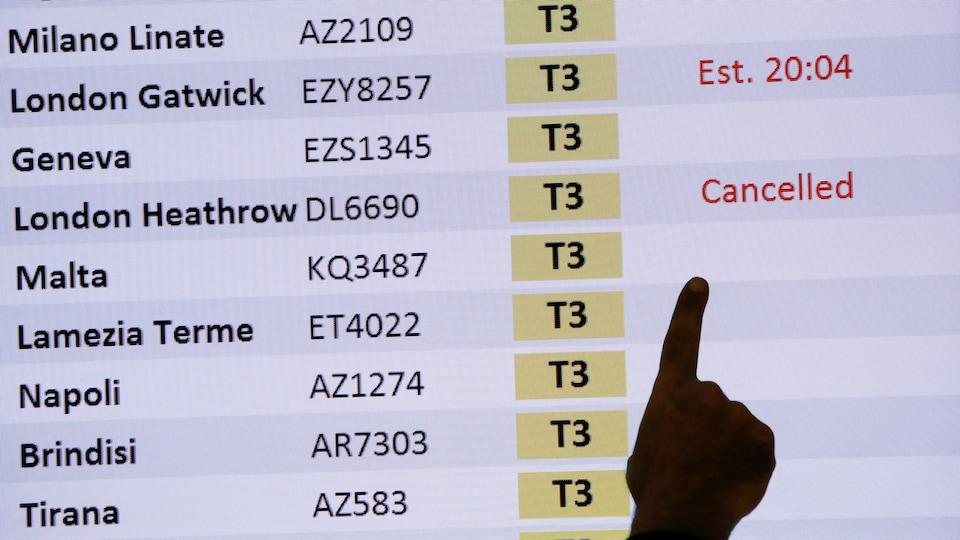 Un tableau des arrivées montre un vol annulé de Londres à l'aéroport de Fiumicino, en Italie.
