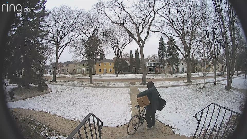 Une image de caméra montre un homme cagoulé, de dos, à bicyclette et tenant un gros colis, au bas de l'escalier extérieur d'une maison.