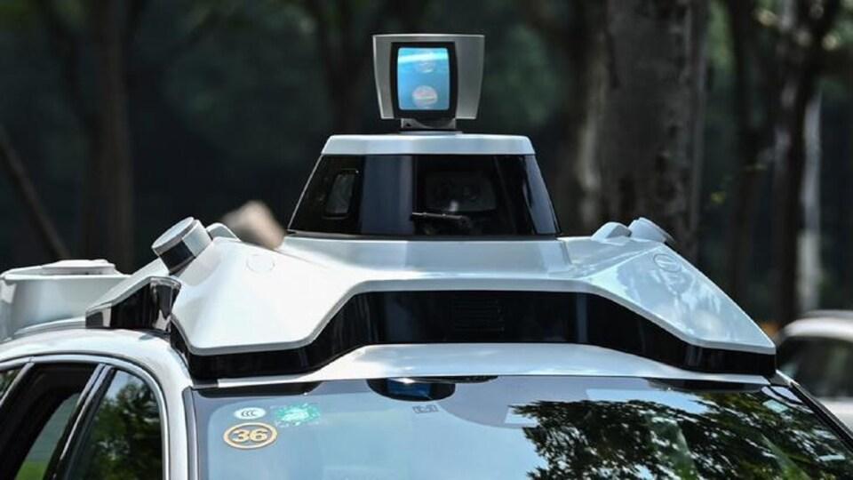 Des caméras et détecteurs sur le haut d'une voiture autonome blanche de marque Volvo.