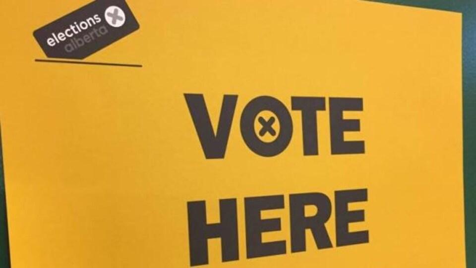 Plan serré d'une pancarte d'Élections Alberta où il est écrit en anglais « Votez ici ».