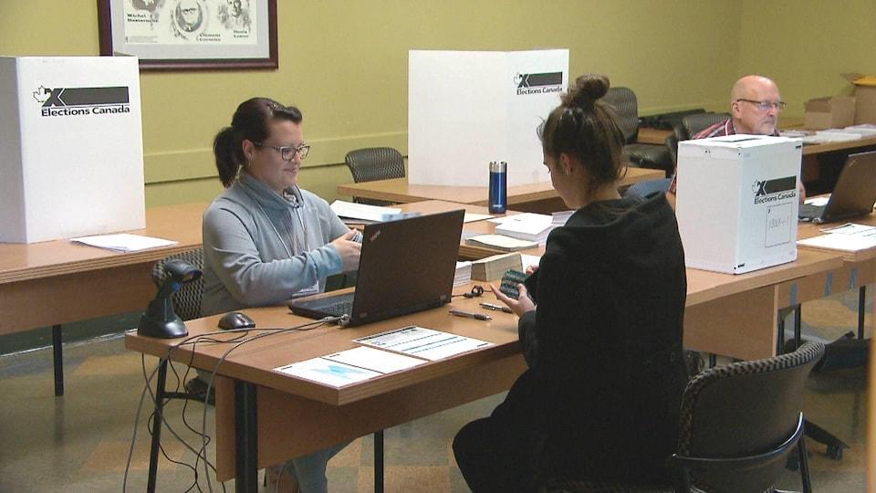 Une scrutatrice vérifie l'identité d'une jeune électrice dans un bureau de vote.