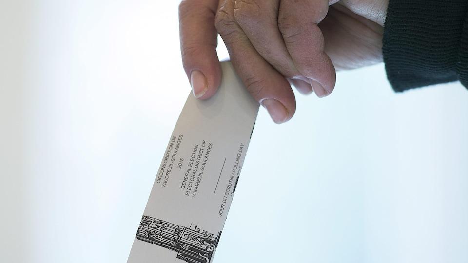 Une personne tient un bulletin de vote pour le déposer dans l'urne.