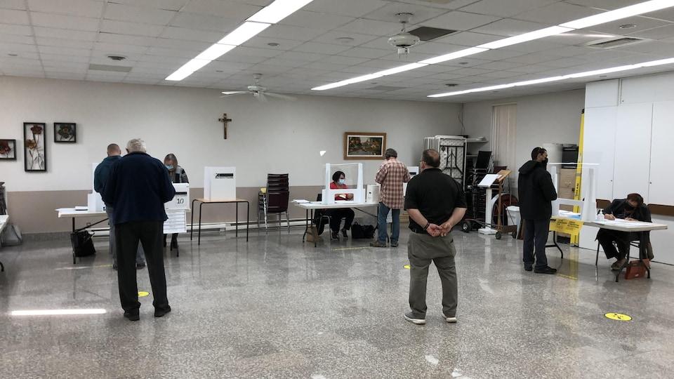 Des électeurs patientent dans un bureau de scrutin.