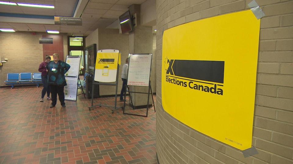 Gros plan sur une affiche jaune collée sur un mur de briques sur laquelle on peut lire le logo d'Élections Canada. En arrière-plan, des pancartes indiquent l'entrée d'un bureau de vote.
