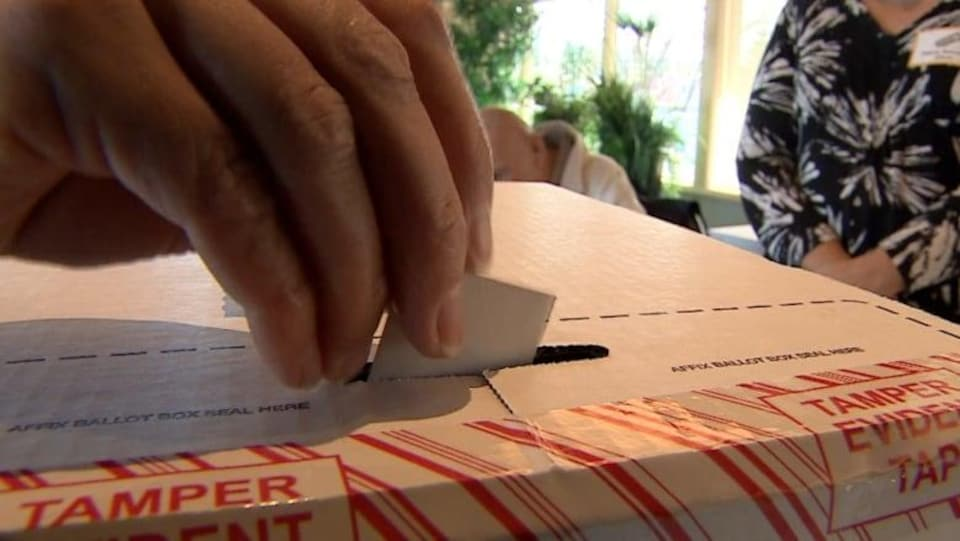 Une main glisse un bulletin de vote dans une urne.
