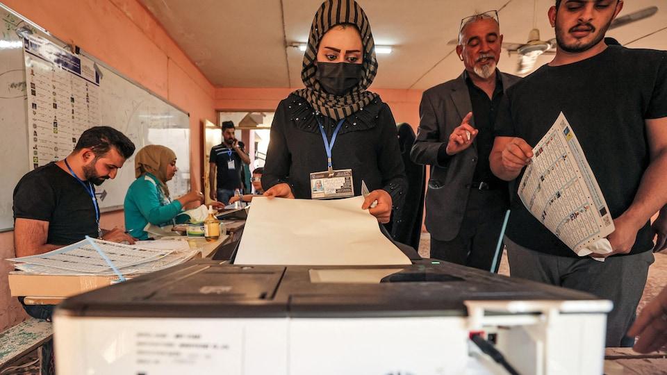 Une femme dans un bureau de vote.