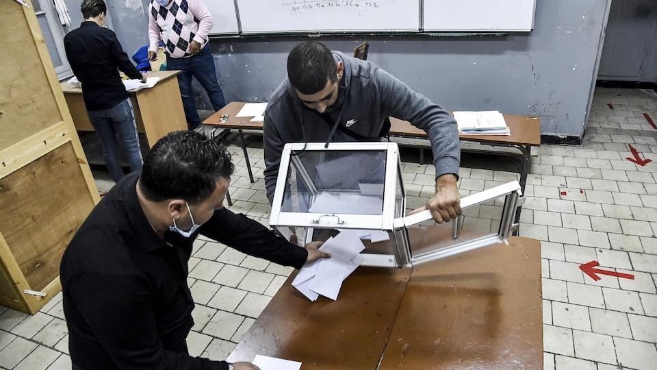 Des employés dans un bureau de vote à Alger vide une urne électorale.