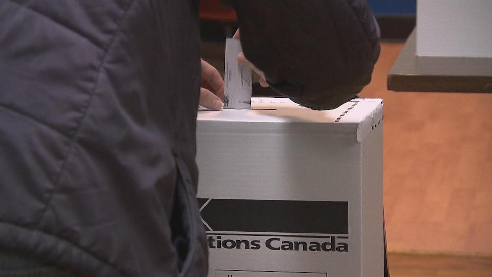 Un électeur dépose son bulletin de vote.