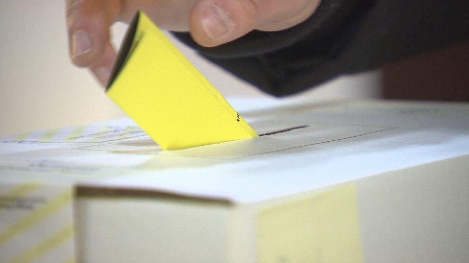 Une main dépose dans la fente d'une boîte de scrutin un bulletin de vote jaune plié en trois parties.