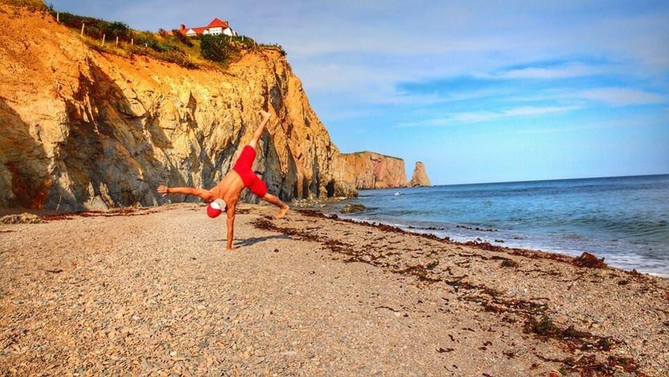 Dominic Gallant en équilibre sur une main sur une plage