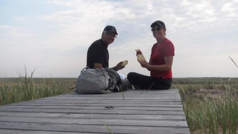 Bernard Caron et Joëlle Pineault assis sur un quai aux Îles-de-la-Madeleine.