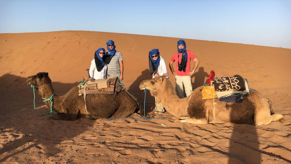 Quatre voyageurs et deux dromadaires dans le désert du Maroc