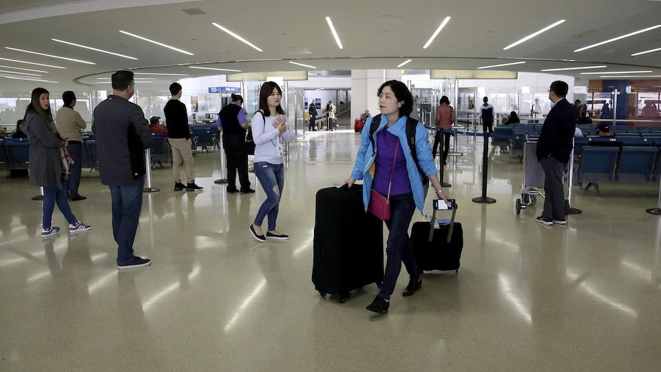 Une voyageuse avec ses bagages à l'aéroport.