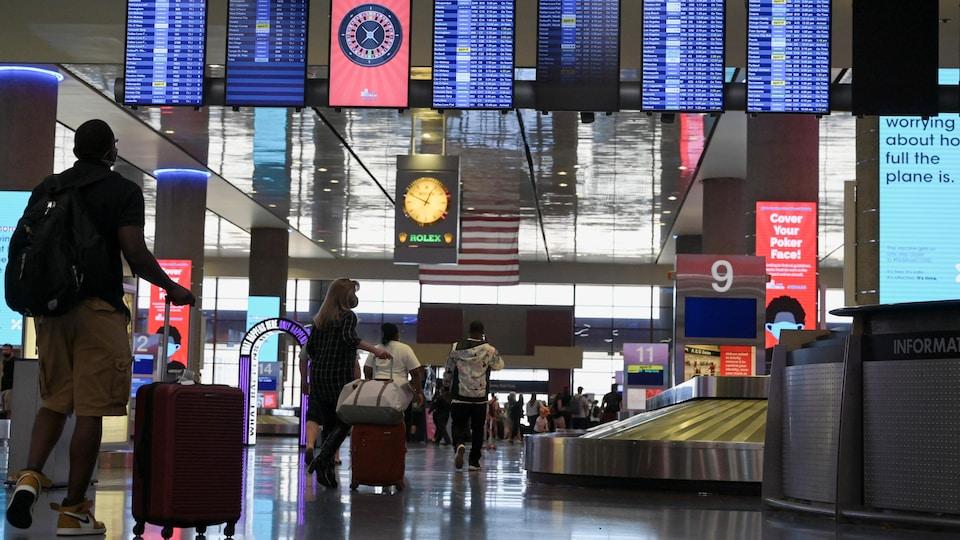 Des voyageurs qui transportent des valises près d'un carrousel à bagages d'un aéroport.
