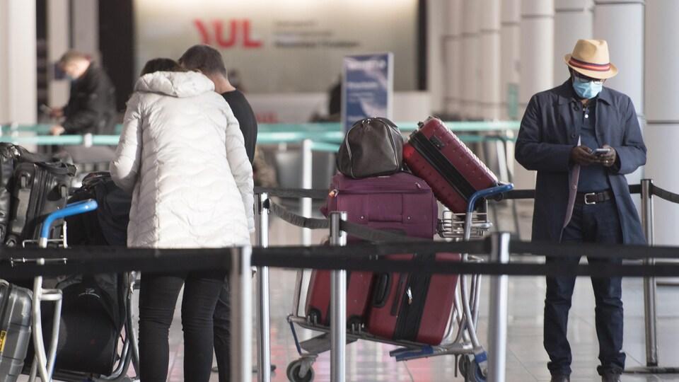 Des voyageurs forment une file d'attente à l'aéroport Pierre-Elliot-Trudeau de Montréal.