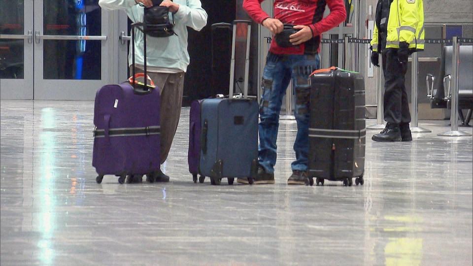 Le bas du corps de deux personnes, avec des valises à leurs pieds