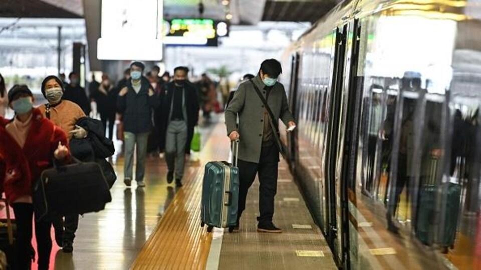 Des personnes portant des masques de protection sur le quai d'une gare de Shanghai le 28 mars 2020.