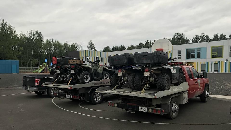 Des véhicules aux couleurs du ministère de la Faune, avec des VTT dans des remorques, garés dans un stationnement d'école, le jour.