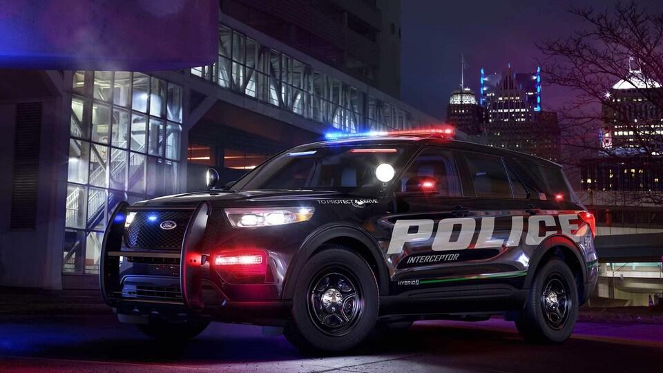 Photo promotionnelle d'un véhicule Ford Police Interceptor Utility. La photo a été prise de soir, dans un décor urbain. Les gyrophares du véhicule sont allumés.