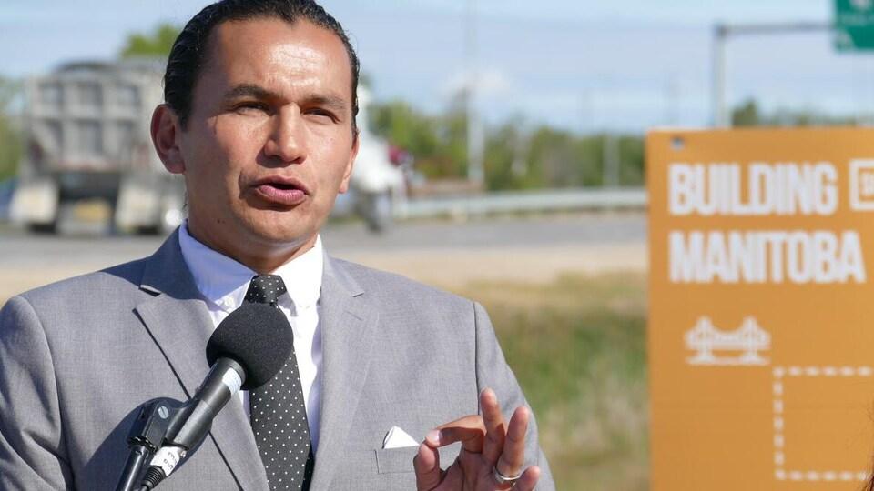 Un homme parle à un micro, à l'extérieur, devant une affiche orange aux couleurs du Nouveau Parti démocratique sur laquelle on peut lire en anglais : Construire le Manitoba.