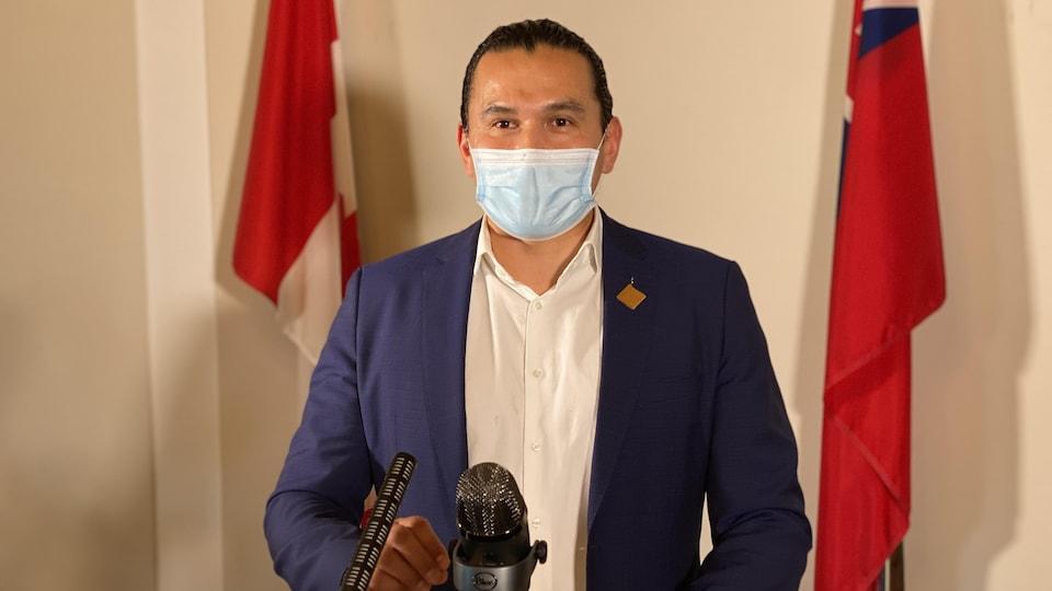 Wab Kinew est debout à un lutrin devant un micro et porte un masque.