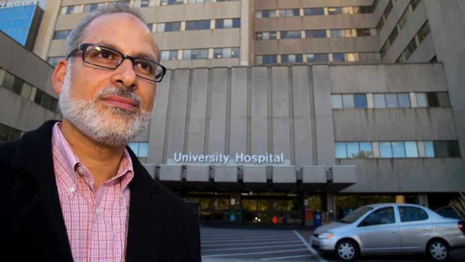 Le médecin portant des lunettes devant un hôpital.