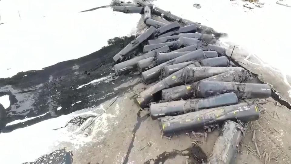 Du pétrole s'écoule de wagons empilés.