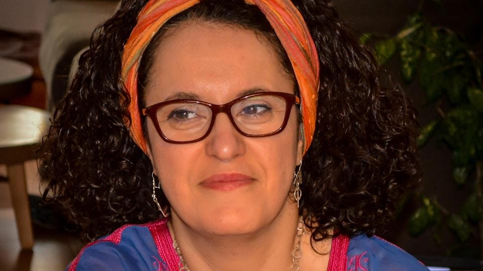 Portrait en couleur de Wahiba Khiari. Elle a les cheveux lâchés et frisés, porte foulard orange en bandeau dans les cheveux, des lunettes et une tunique brodée mauve et rose.