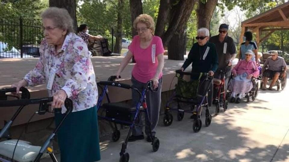 Des personnes âgées marchent en se suivant.