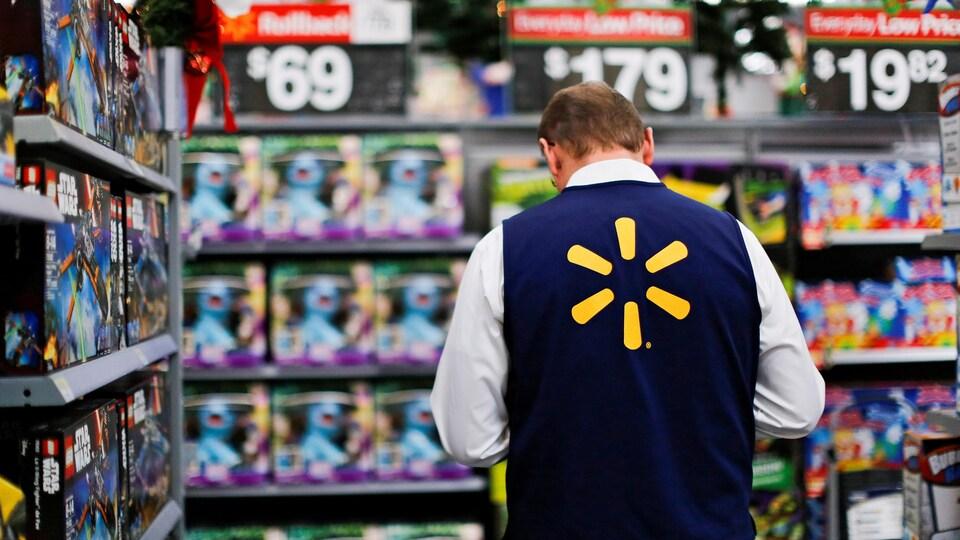 Un employé parmi des jouets dans un magasin de Walmart.
