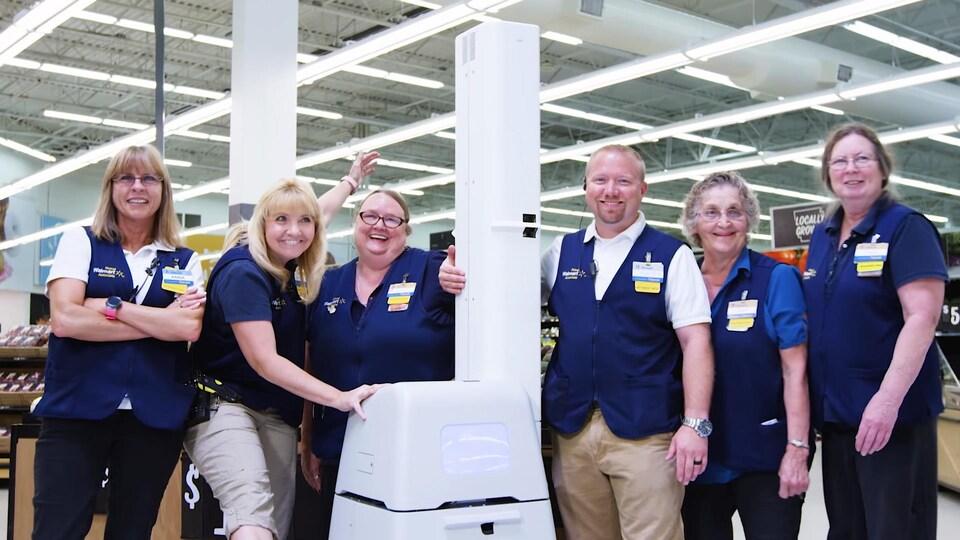Des employés de Walmart posent autour d'un petit robot blanc en forme de boîte.