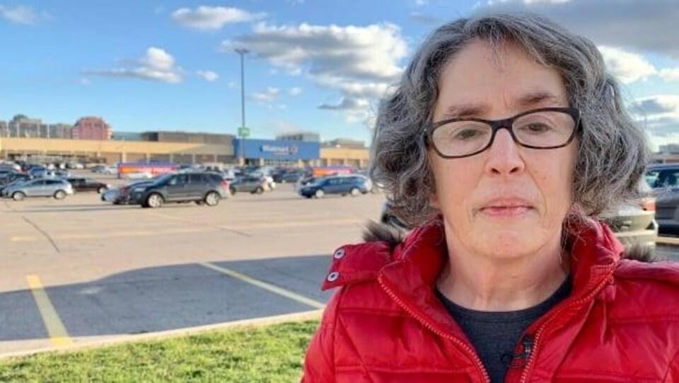 Une cliente devant un stationnement Walmart.