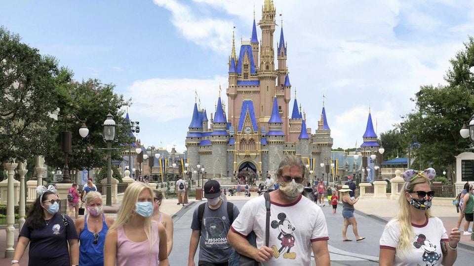 Des gens masqués marchent devant le château emblématique du parc d'attractions.
