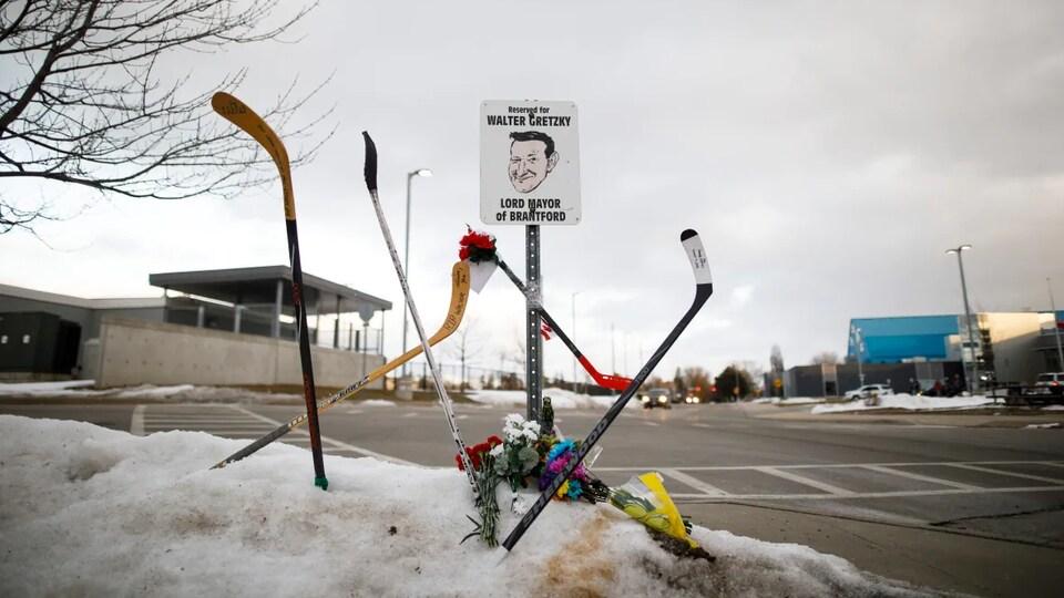 Des bâtons de hockey, des cartes et des fleurs sont vus sur un banc de neige à côté de la place de stationnement réservée de Walter Gretzky au centre sportif Wayne Gretzky à Brantford, en Ontario, vendredi, après l'annonce de la mort de Walter.