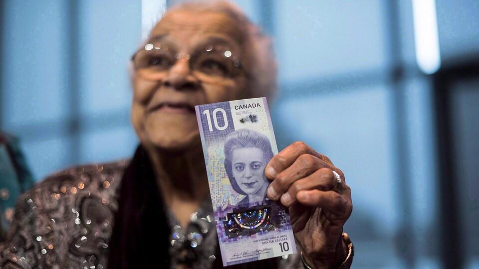 Une femme âgée assise dans un fauteuil roulant exhibe fièrement le billet de 10 dollars canadiens où on voit l'effigie de Viola Desmond à la verticale.