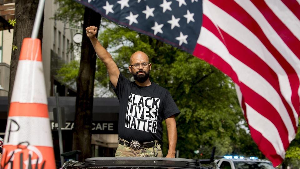 Un homme porte un t-shirt sur lequel on peut lire « Black Lives Matter ».