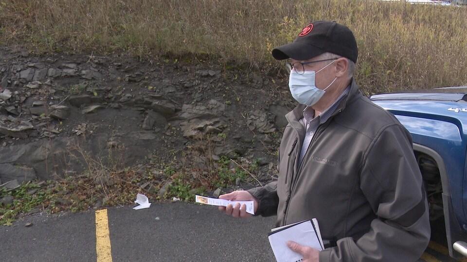 Un homme masqué avec dans une main un calepin et dans l'autre son permis de chasse.