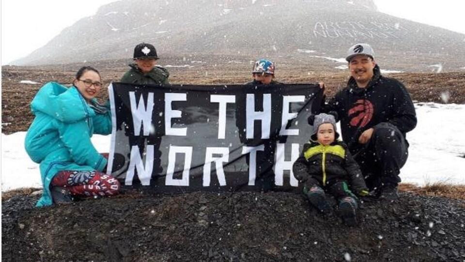 Une famille pose avec un drapeau We the North dans la nature, au Nunavut, sous la neige.