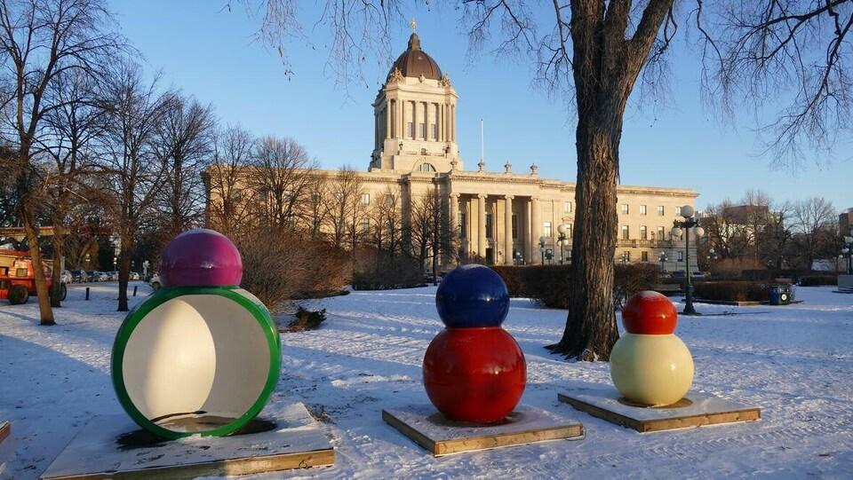 Des petites cabanes qui ressemblent à des bonshommes de neige colorés devant le palais législatif.