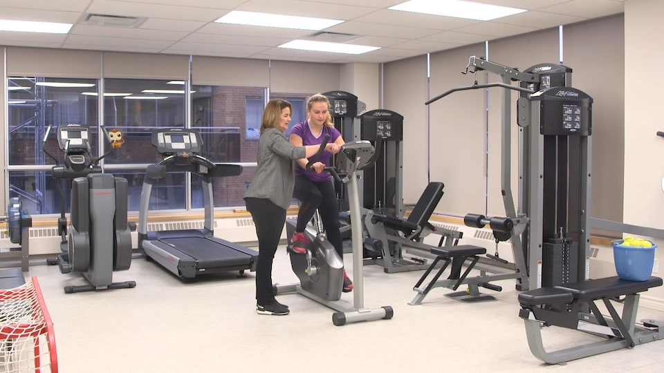Une femme est assise sur un vélo stationnaire dans une salle d'entraînement, une autre lui donne des instructions.