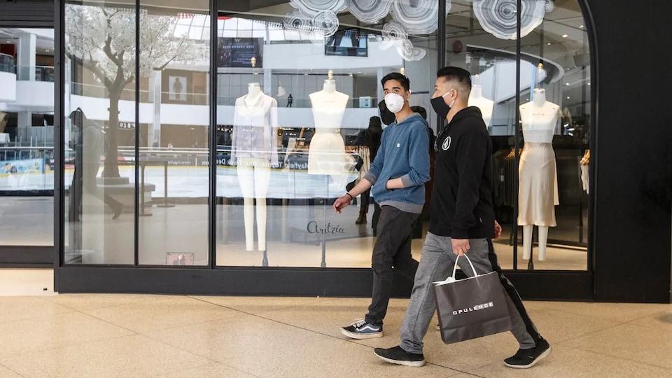 Deux clients marchent devant un magasin de vêtements. Ils portent chacun un masque sur leur visage.