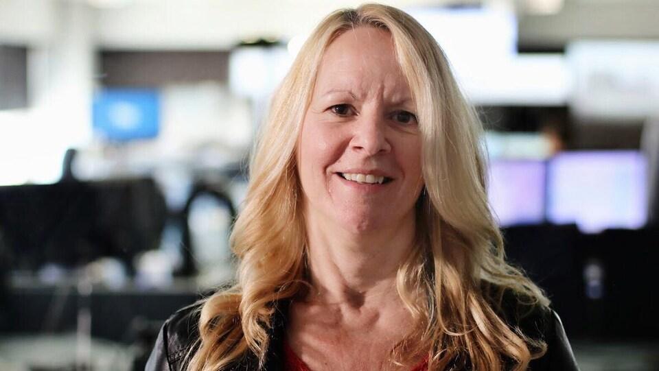Une femme blonde sourit dans une salle pleine d'écrans d'ordinateur.