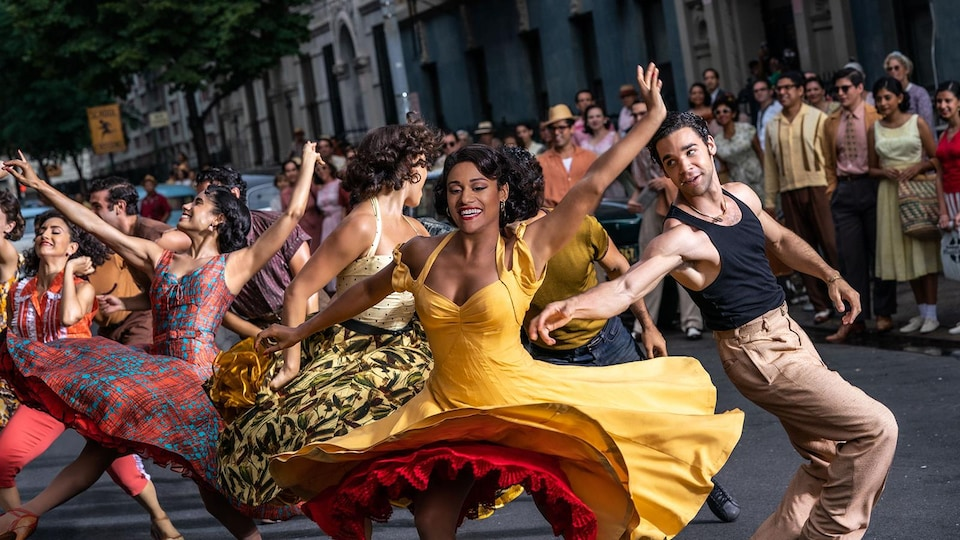 Plusieurs personnes dansent dans une rue sous l'œil d'autres personnes réunies sur le trottoir.