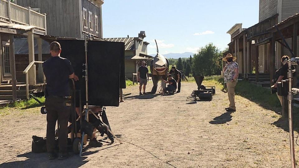 Des cinéastes sur un plateau de tournage de style western avec des vieux édifices.