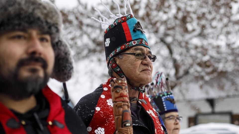 Trois chefs autochtones portant des tenues traditionnelles marchent dans une rue enneigée.